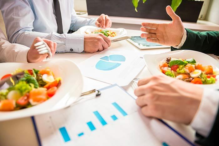 Trabajador por cuenta propia comiendo junto a unos clientes potenciales