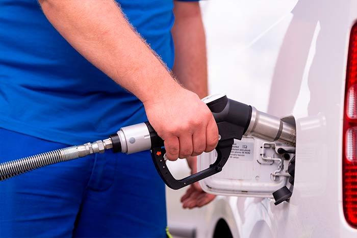 Trabajador repostando gasolina en el coche de empresa