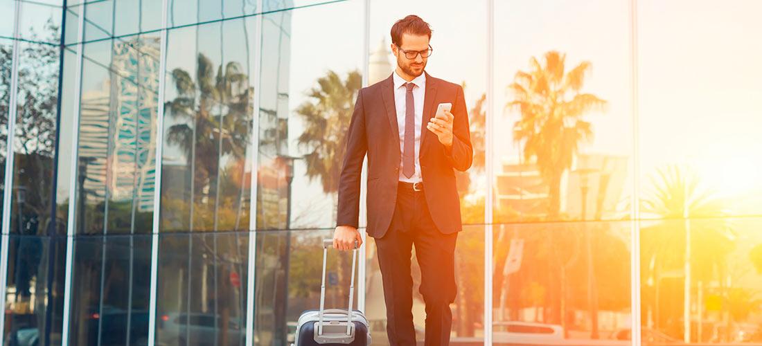 Trabajador de empresa saliendo de un hotel durante un viaje de negocios